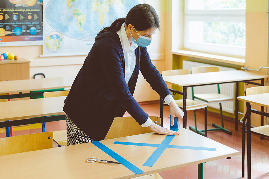 Teacher wearing a mask taping desk